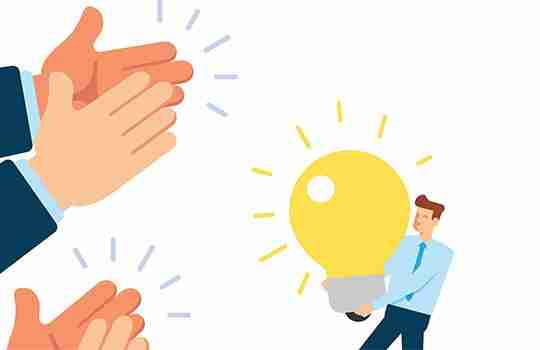 people clapping a man holding a large light bulb to represent the concept of having employees share ideas